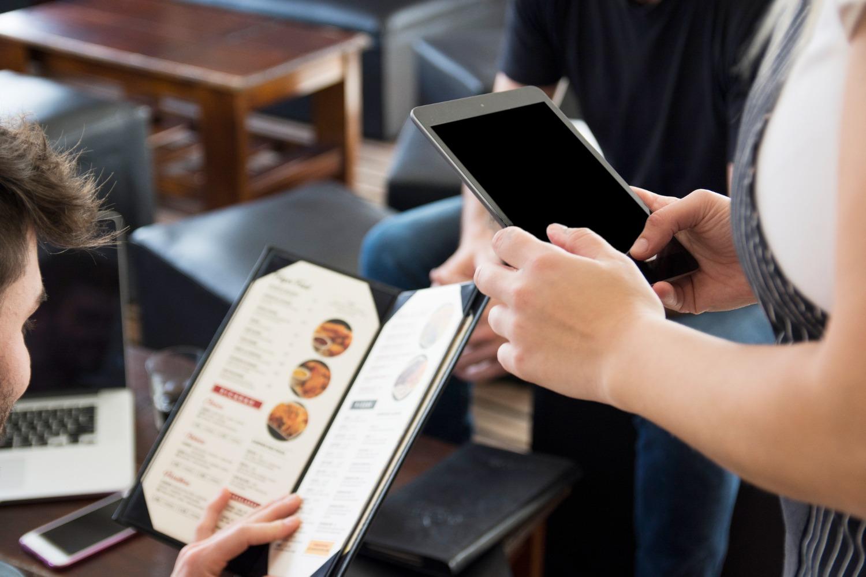 waitress-using-digital-tablet-while-taking-order-restaurant